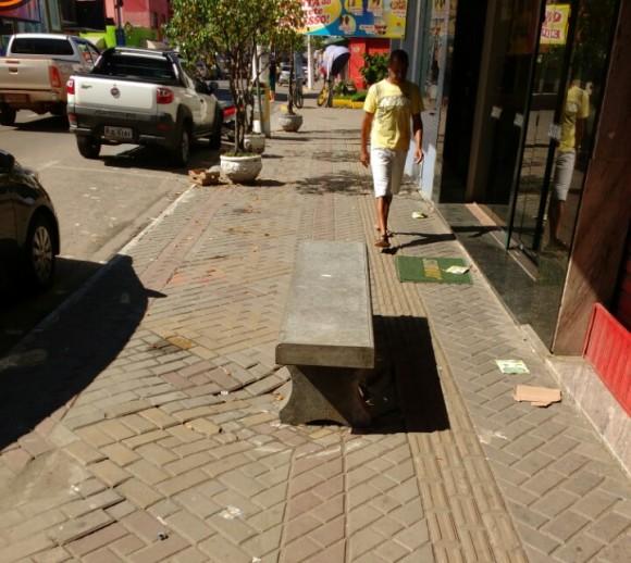 """Na Avenida do Cinquentenário, parte da calçada está afundando há mais de uma semana. Como a Secretaria de Desenvolvimento Urbano não apareceu para dar uma solução, comerciantes e transeuntes resolveram """"sinalizar"""" o local de forma inusitada: colocaram um banco como forma de prevenir acidentes (Foto Pimenta)."""
