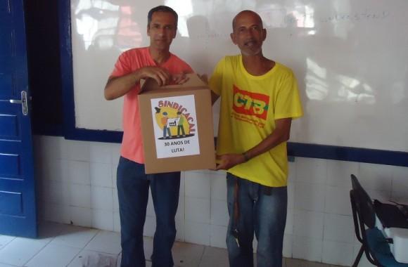 Fernandes, de amarelo, entrega kit a associado do Sindicacau.